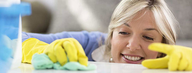 Smiling maid wearing yellow gloves carefully cleaning a countertop in a Chicago home